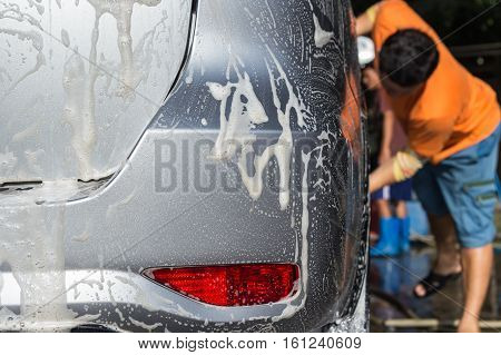 A Man Using Soap For Car Washing In Car Care Shop
