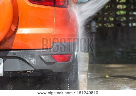 Man Spraying Pressure Washer For Car Wash In Car Care Shop. Focus On Car