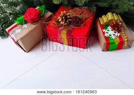 Christmas background with decorated gift boxes and Christmas tree branches. Christmas background with fir branches and kraft paper wrapping presents. Copy space.
