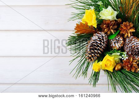 Christmas background with golden pine cones and yellow fabric roses. Christmas table centerpiece. . Christmas decoration with fir branches and pine cones. Copy space.