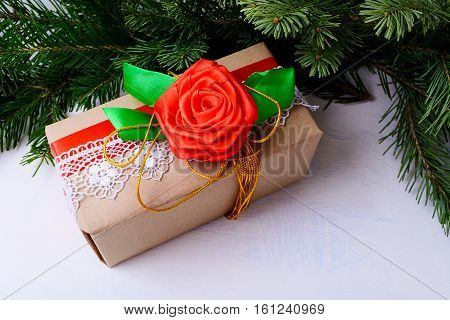 Christmas gift box decorated with lace and red silk rose. Christmas background with fir branches and kraft paper wrapping present.