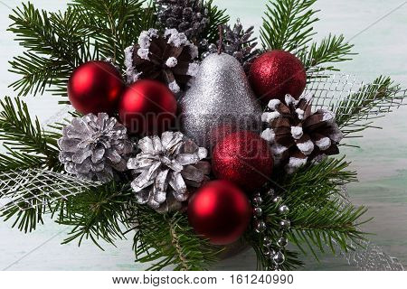 Christmas red baubles silver glitter pear and decorated pine cones. Christmas decoration with fir branches and red ornaments. Christmas table centerpiece.