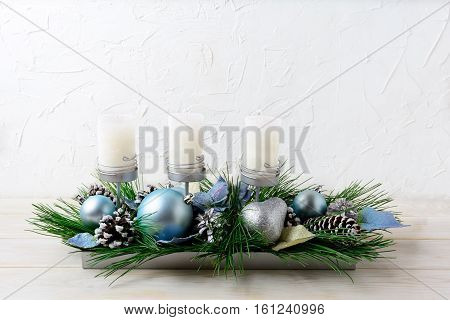 Christmas table centerpiece with three candles and blue ornaments. Christmas decoration with blue baubles. Christmas greeting background. Copy space.
