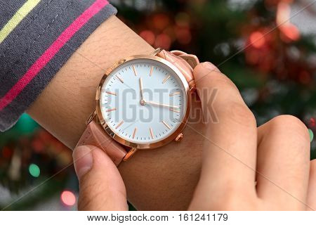 Girl's hand with wrist watch in Christmas time in front of Christmas tree in background