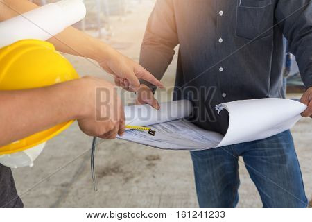 Engineer And Architect Working At Construction Site With Blueprint