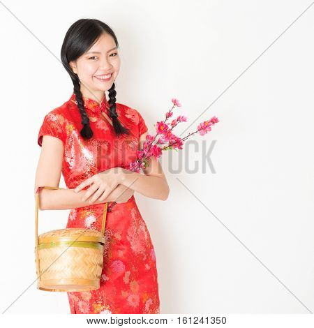 Young Asian woman in traditional cheongsam dress holding gift basket and plum blossom smiling, celebrating Chinese Lunar New Year or spring festival, standing on plain background.