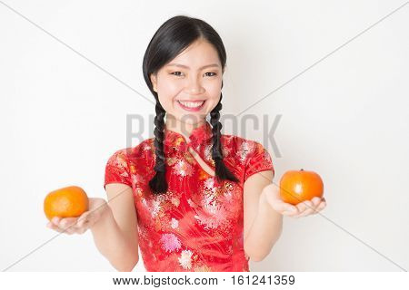 Young Asian woman in traditional cheongsam dress holding mandarin orange and smiling, celebrating Chinese Lunar New Year or spring festival, standing on plain background.