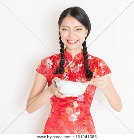 Portrait of young Asian girl in traditional qipao dress eating, hand holding bowl and chopsticks, celebrating Chinese Lunar New Year or spring festival, standing on plain background.