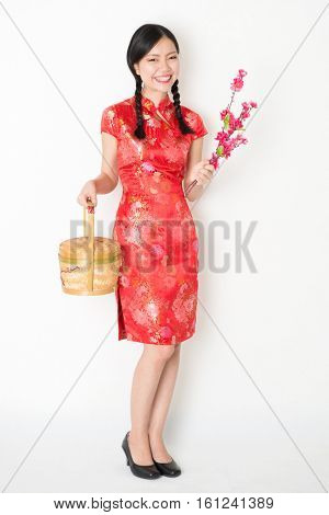 Young Asian woman in traditional qipao dress holding gift basket and plum blossom smiling, celebrating Chinese New Year or spring festival, full length standing on plain background.