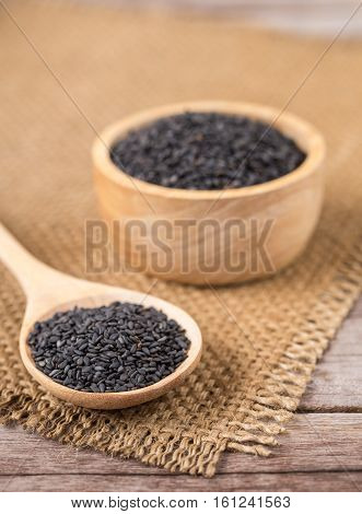Close Up Black Sesame In Bowl And Spoon On Wooden Plank