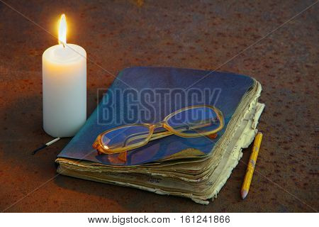 Candle And Old Notebook Lying On An Old Metal.
