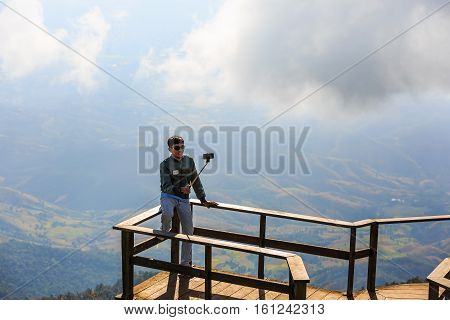 CHIANG MAI THAILAND - 06 NOVEMBER 2016 - Unidentified tourist takes his own portrait photograph (selfie) with his mobile phone at Kew Mae Pan panoramic vantage point.