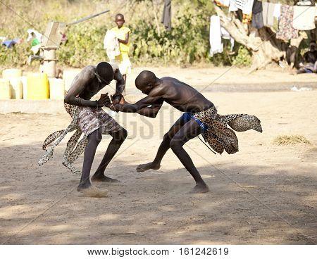 BOR, SOUTH SUDAN-DECEMBER 4, 2010: Unidentified Dinka tribesmen wrestle in a small village north of Bor, South Sudan