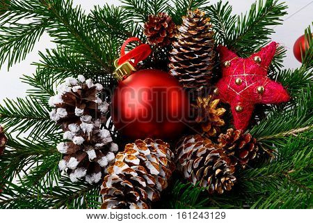 Christmas red ornaments golden pine cones and rustic star. Christmas decoration with fir branches and red baubles. Christmas table centerpiece.