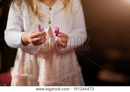 child, hands close-up, flowers, white sweater a solar flare
