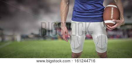 3D Sports player holding ball against gloomy sky