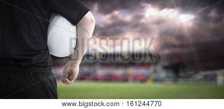3D Rugby player holding a rugby ball against gloomy sky
