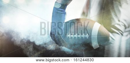 3D Cropped image of sportsman holding American football ball ball against digitally generated image of color powder