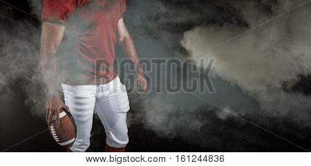 3D American football player with ball against digitally generated image of color powder