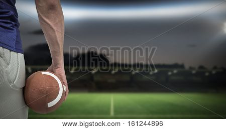 3D Close-up of American football player holding ball against rugby pitch