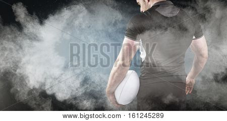 3D Tough rugby player holding ball against digitally generated image of color powder