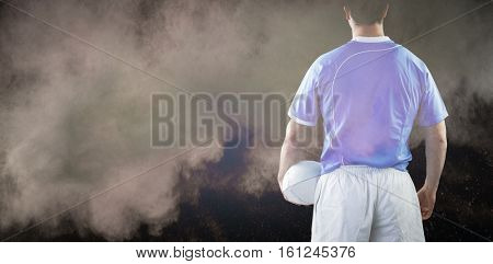3D Rugby player holding a rugby ball against splashing of powder