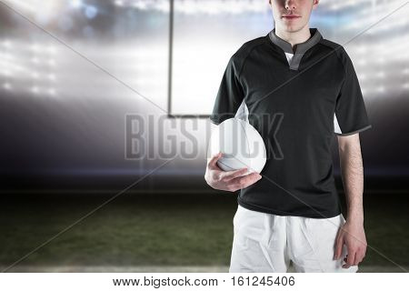 3D Rugby player holding a rugby ball against american football arena