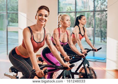 Young women exercising on stationary bicycles in fitness gym