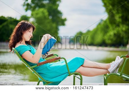 Woman In Green Dress Reading A Book In Tuileries Garden Of Paris, France