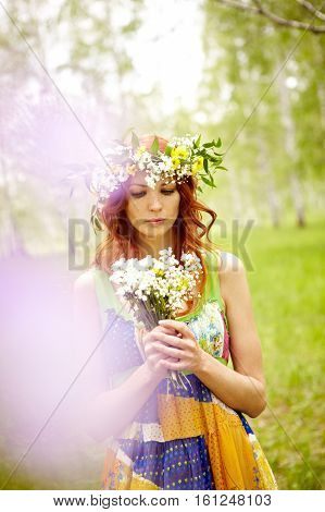 Pensive woman in sundress holding flower bouquet