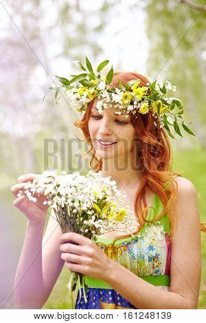 Beautiful woman in flower crown arranging wildflower bouquet