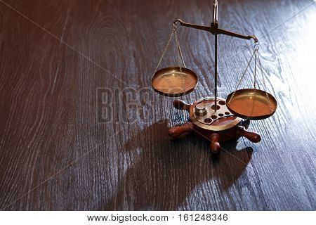 Old brass weight scales on dark wooden background with free space