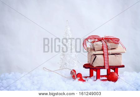 red toy sled with a pile of gifts christmas ball snow retro style background