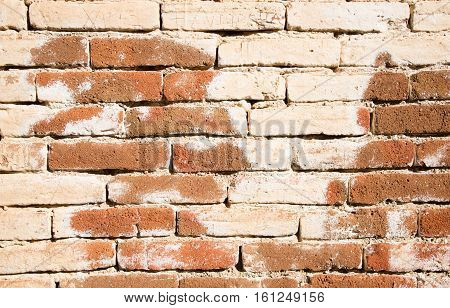 Old barrier wall background with clay bricks in white and brown color.
