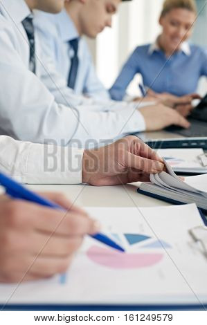 Male hand turning over pages of financial report