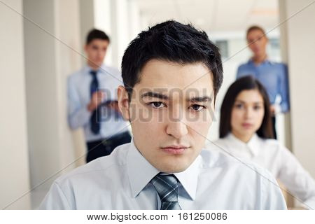 Portrait of young serious businessman looking at camera with his colleagues behind