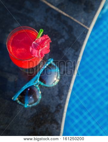 Water-melon fresh fruit smothie drink with sunglasseson the swimming pool border - holiday tropical concept