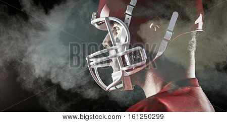 American football player looking at camera against digitally generated image of color powder