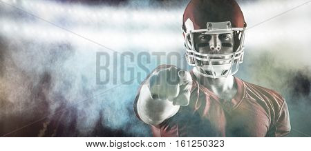 3D American football player pointing at camera against splashing of blue color powder