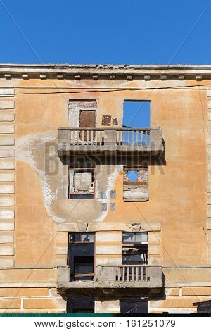 Abandoned building - broken tenement apartment house in daylight