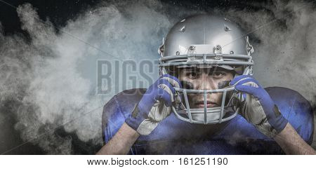3D Portrait of American football player wearing helmet against digitally generated image of color powder