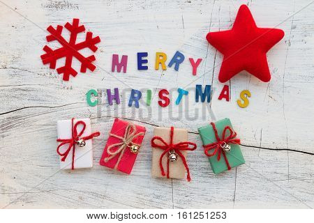 """""""Merry Christmas"""" letters Christmas decoration and gift boxes on white wooden background flat laying in top view"""