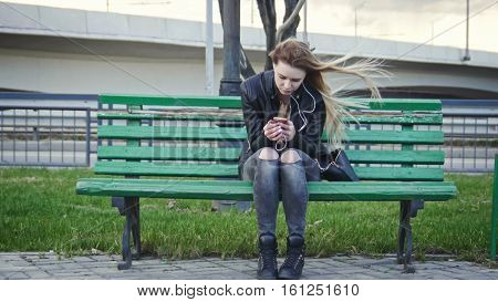 Dissapointed girl with long blonde hair in leather jacket straightens hair use gadget sitting on the bench in the wind listen headphones, wide angle, front view, telephoto