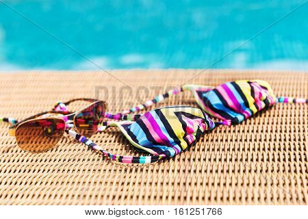 Sunglasses and colorul swimwear near swimming pool poster