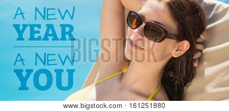 Cheerful woman by swimming pool against new year new you