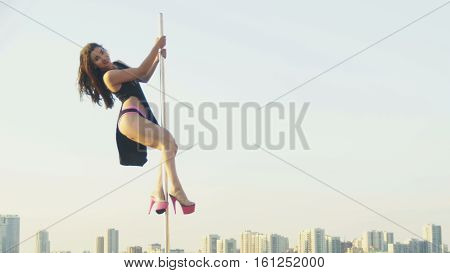 Fit attractive girl dancing near portable pole at summer day over the skyline, slow-motion, near river