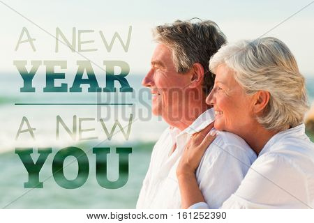 New year new you against woman hugging her husband while standing at beach