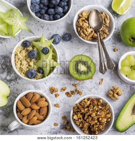 Ingredients for a healthy breakfast, avocado, quinoa bowl, carambola, green apple, banana, kiwi, nuts, oatmeal, berries, fruits, blueberry, almonds walnuts The concept of natural organic food in season Top view. Color greenery
