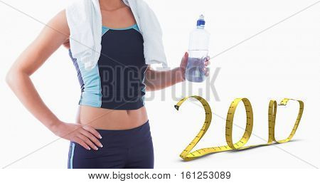 3D Midsection of sporty woman with towel around neck and water bottle against 2017 made of measuring tape