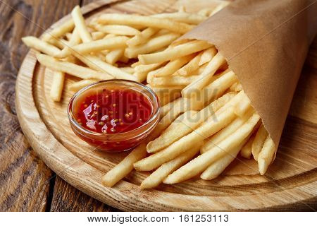 French fries wrapped in brown craft paper, closeup. Fast food take away on rustic wood. Fried potato chips with tomato sauce.